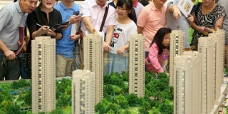 Prospective customers examin a model of a new residential compound at a real estate office in Hangzhou, Zhejiang Province